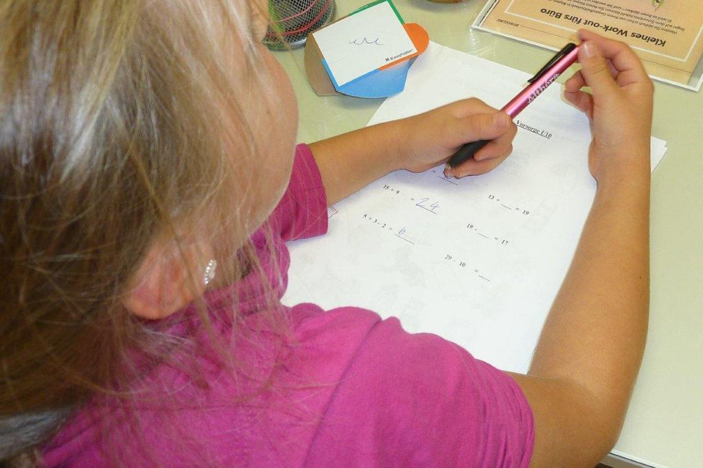 Mädchen bei Mathe-Aufgaben während einer U10-Untersuchung