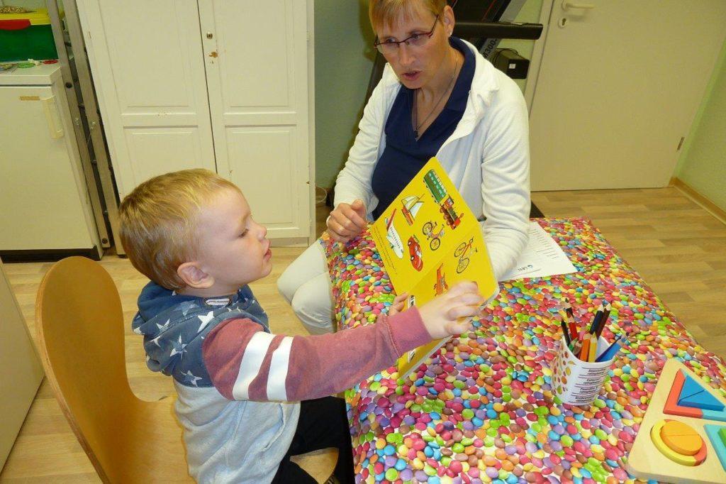 Kind schaut ein Buch bei U7a Untersuchung